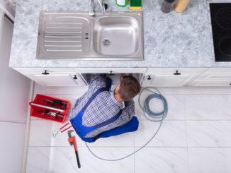 Klempner arbeitet mit Spiral am Abfluss